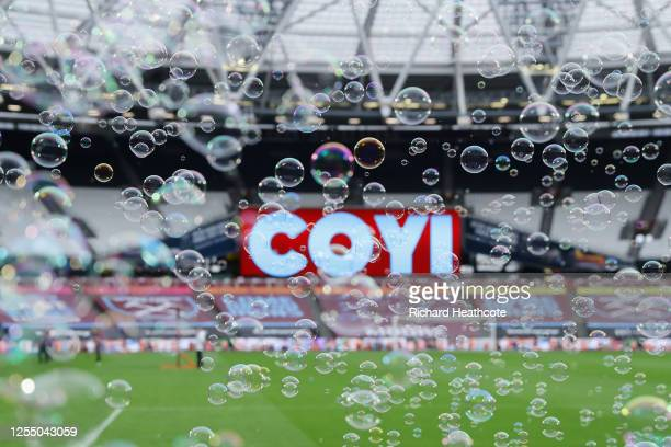 Both teams enter the pitch amongst bubbles during the Premier League match between West Ham United and Burnley FC at London Stadium on July 08, 2020...