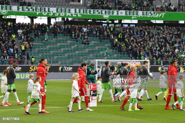 Both teams enter the pitch as the stand of the Wolfsburg Ultras is empty due to a protest during the Bundesliga match between VfL Wolfsburg and FC...