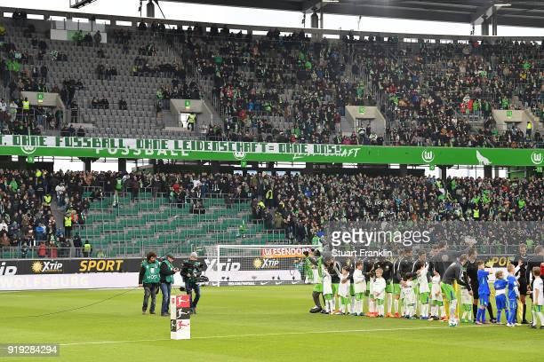 Both teams line up as the stand of the Wolfsburg Ultras is empty due to a protest during the Bundesliga match between VfL Wolfsburg and FC Bayern...