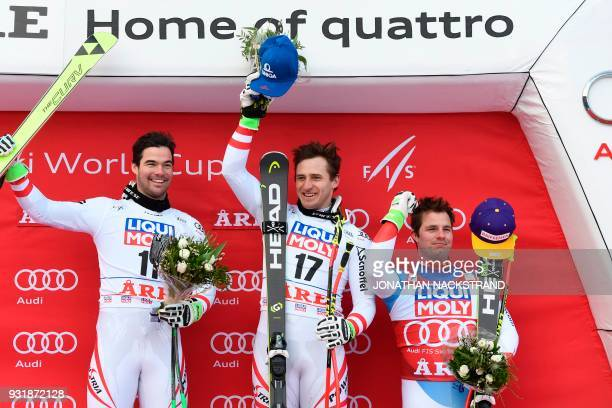 Both winner Austria's Vincent Kriechmayr Austria's Matthias Mayer and 3rd place Switzerland's Beat Feuz celebrate on the podium after the Men's...