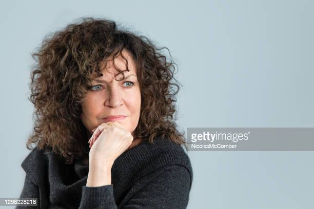 bothered frowning female in her early 60s looking right in front of a gray wall - hand on chin stock pictures, royalty-free photos & images