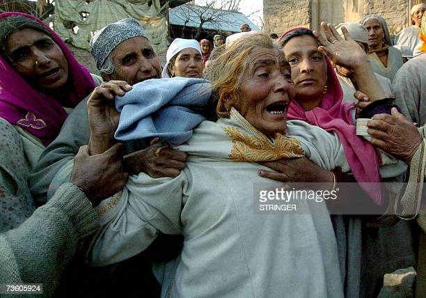 A Kashmiri woman is comforted as she grieves near the body of her relative Gulam Nabi during his funeral cermony in Botingoo some 56kms north of...
