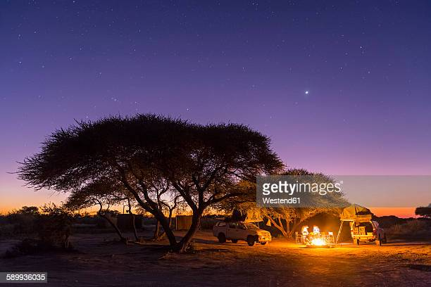 Botswana, Kalahari, Central Kalahari Game Reserve, campsite with campfire under starry sky