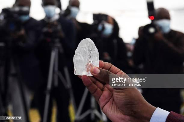 Botswana member of cabinet holds a gem diamond in Gaborone, Botswana, on June 16, 2021. - Botswanan diamond firm Debswana said on June 16, 2021 it...