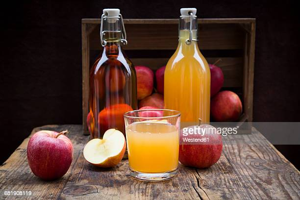 Bottle and glass of apple juice, cloudy and clear, red apples on wood