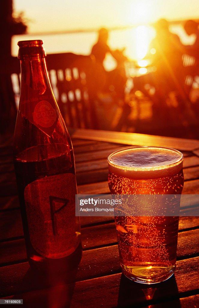 Bottle and glass of beer by Lake Vattern at sunset, Motala, Ostergotland, Sweden, Europe : Bildbanksbilder