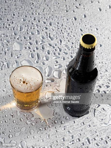 Bottle and glass of beer I fill on a table.