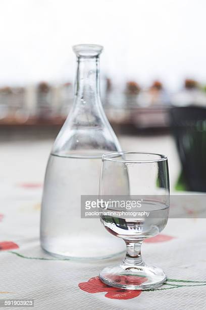Bottle and glass with mineral water on the table