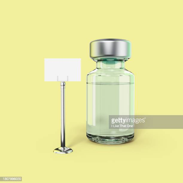 a bottle containing medical liquid stands alone next to a reserved sign stand on a pale yellow backdrop, low angle view - atomic imagery stock pictures, royalty-free photos & images