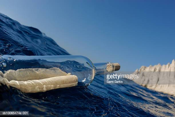 Bottle containing message floating in sea, close-up