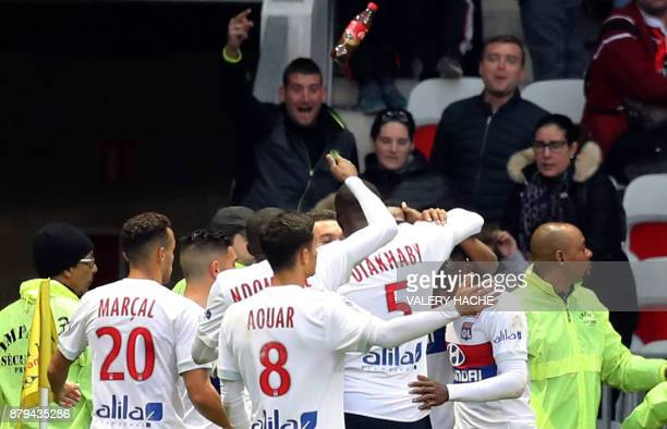 A bottle flies through the air as Lyon's French forward Myziane Maolida celebrates with teammates after scoring a goalduring the French L1 football...