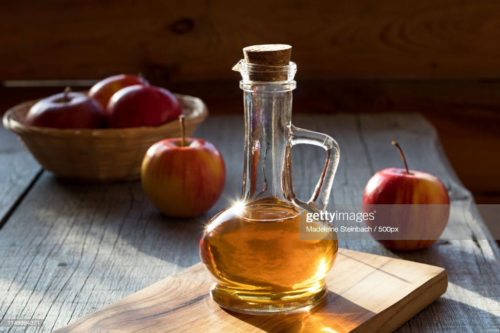 A Bottle Of Apple Cider Vinegar With Apples In The Background : Foto de stock
