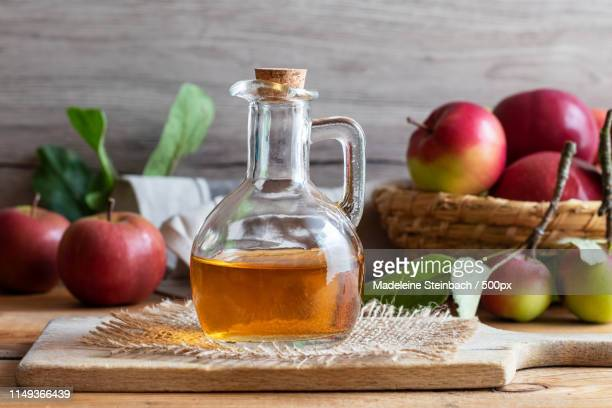 a bottle of apple cider vinegar with fresh apples - harvest table stock pictures, royalty-free photos & images