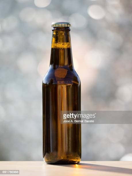 Bottle of beer of crystal with metallic cap on a table outdoors illuminated by the light of the Sun