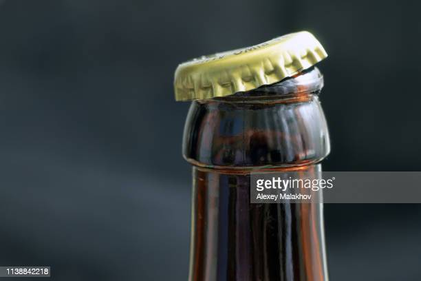 bottle of beer opens on a dark background close-up - cap stock pictures, royalty-free photos & images