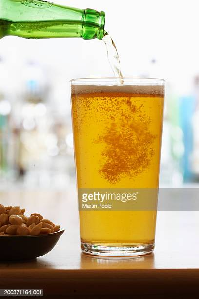 Bottle of beer pouring into pint glass
