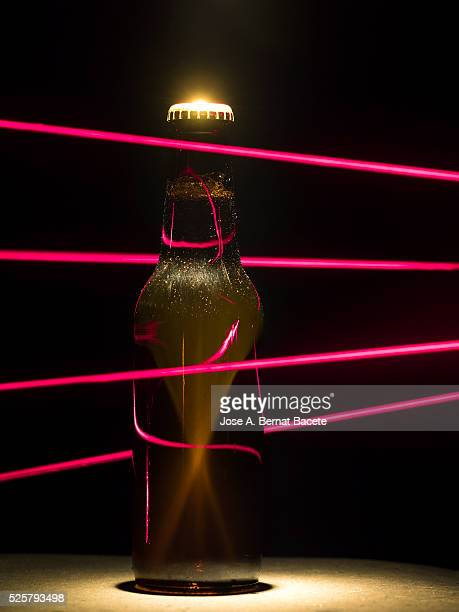 Bottle of beer protected by a trap with beams laser of red color