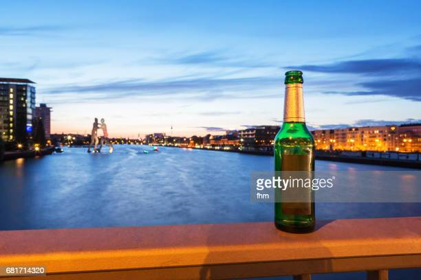 Bottle of beer with Berlin skyline at blue hour in the background (Berlin, Germany)