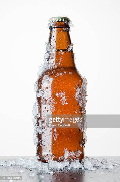 bottle of beer with frosted ice - frio fotografías e imágenes de stock