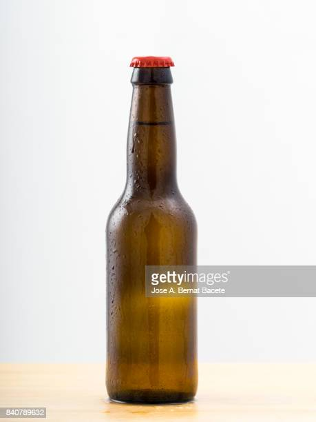 Bottle of beer with the frosted glass with drops of water  on a white background