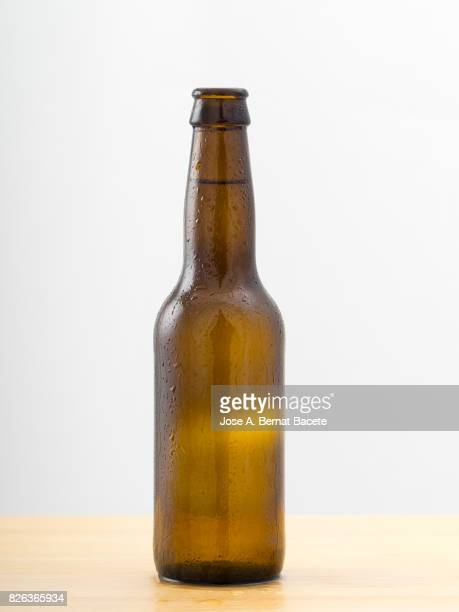 bottle of beer with the glass esmerilado with drops of water and a steam cloud frozen on a white bottom - braun stock-fotos und bilder