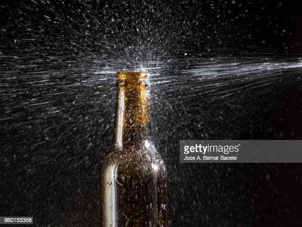 Bottle of beer with the glass esmerilado with drops of water and a steam cloud frozen on a black bottom