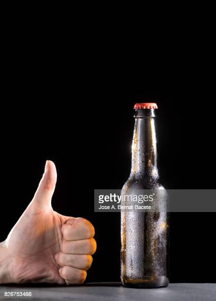 Bottle of beer with the glass esmerilado with drops of water and the hand of a man with  thumb up on a black background