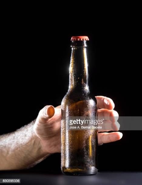 Bottle of beer with the glass esmerilado with drops of water and the hands of a man grab  on a black background