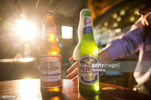 A bottle of Budweiser beer brewed by AnheuserBusch InBev NV left stands next to a bottle of Peroni beer brewed by SABMiller Plc in The Capitol a JD...