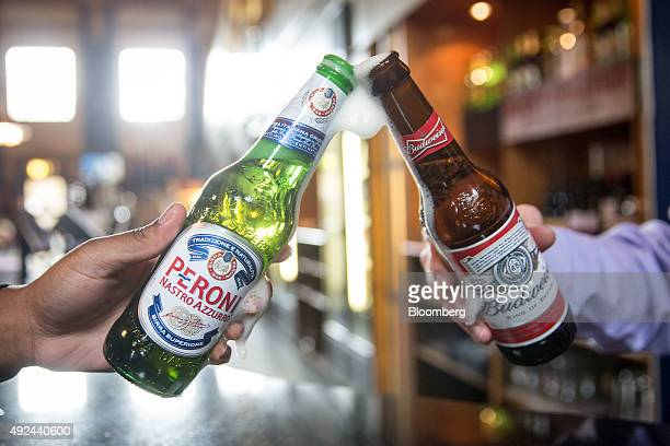 A bottle of Budweiser beer brewed by AnheuserBusch InBev NV right and a bottle of Peroni beer brewed by SABMiller Plc are raised together in The...