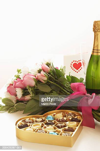 Bottle of champagne by bouquet of flowers and box of chocolates