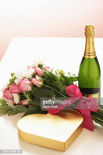 Bottle of champagne by bouquet of flowers and heart shaped box