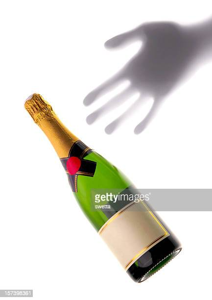 bottle of champagne with hand's shadow
