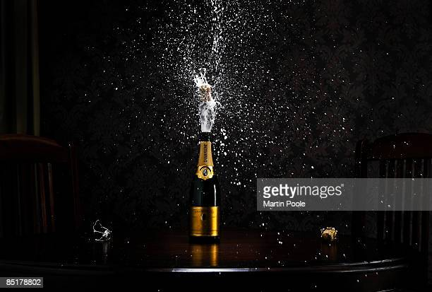 bottle of champange on table exploding cork - champagne stock pictures, royalty-free photos & images