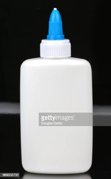 bottle of children's art and craft glue bottle on a black background - volume fluid capacity stock pictures, royalty-free photos & images