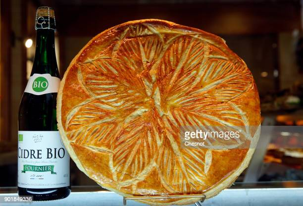 A bottle of cider and an Epiphany cake or Twelfth Night cake are on display in the window of a pastry shop on January 06 2017 in Paris France The...
