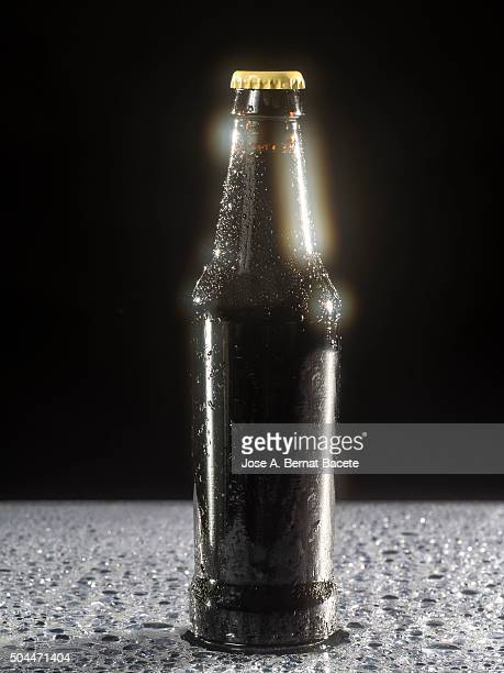 Bottle of cold beer on a table with water drops