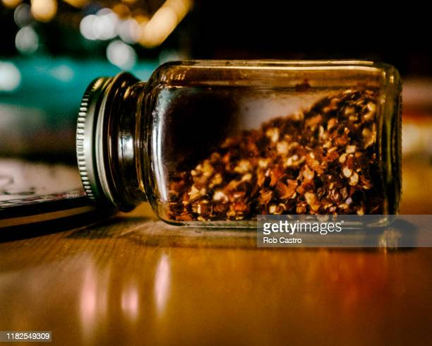 bottle of crushed red hot chili peppers - rob castro stock pictures, royalty-free photos & images