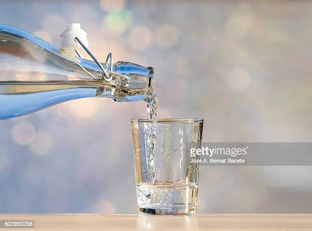 Bottle of crystal with water filling a glass on a table