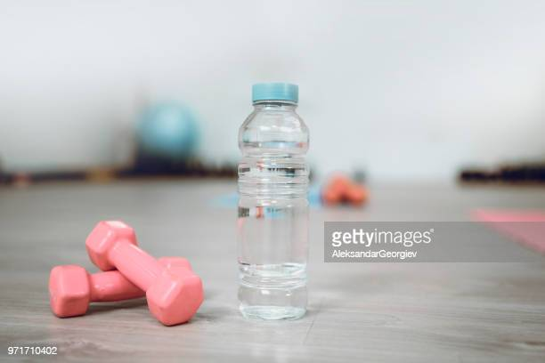 a bottle of fresh water and dumbbells in gym - mat stock pictures, royalty-free photos & images