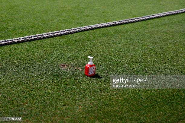 Bottle of hand sanitiser is seen beyond the boundary rope on the pitch during the friendly county cricket match between Surrey and Middlesex at the...