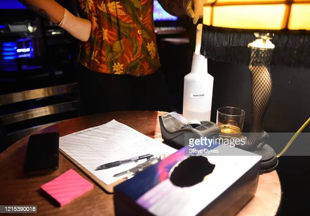 A bottle of hand sanitizer sits on a table next to a clipboard used to track deliveries in the Lucky Devil on March 27 2020 in Portland Oregon The...