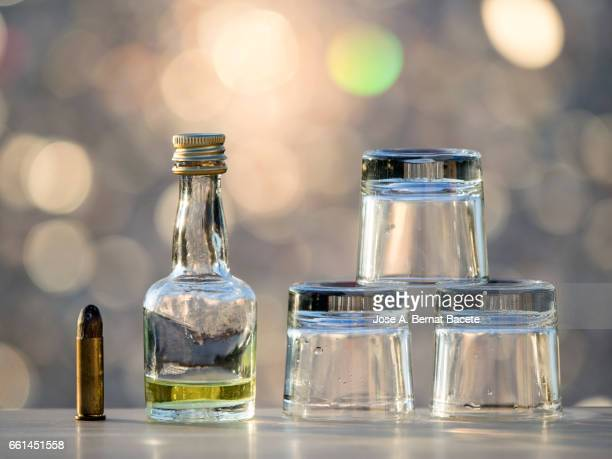 Bottle of liqueur and  glasses of chupito close to a bullet , concept of which the alcoholism kills