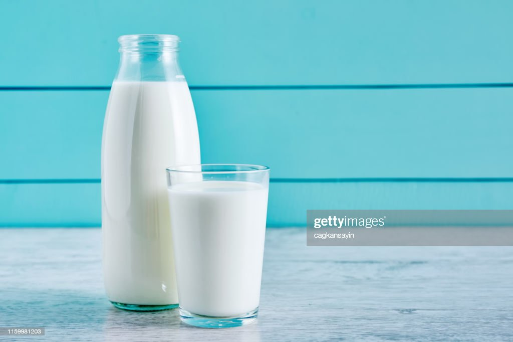 Bottle of milk and a glass full of milk on a wooden table against turquoise wooden background. Close up view. : Stock Photo