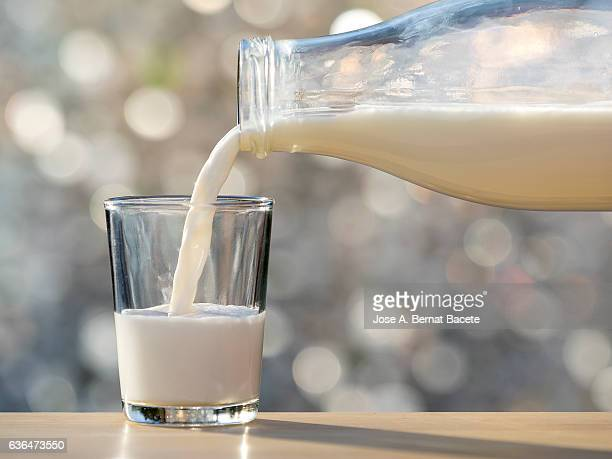 bottle of milk of crystal filling a glass of milk, illuminated by the natural light of the sun - milk bottle stock pictures, royalty-free photos & images