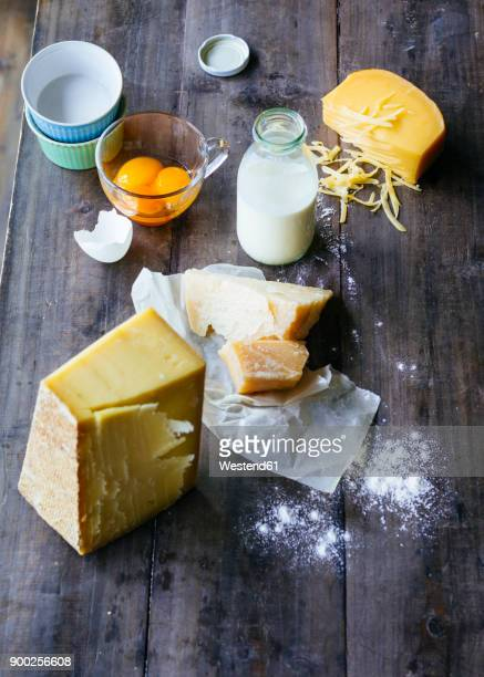 Bottle of milk, pieces of cheese and glass of egg yolks on wood