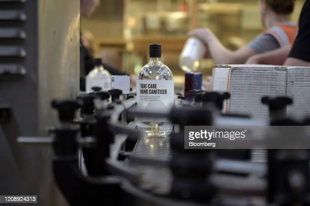 Bottle of of Four Pillars Take Care hand sanitizer moves along a conveyor on the bottling line at the Four Pillars Gin Distillery in Healesville,...