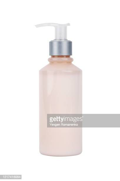 bottle of pink cosmetic moisturizer isolated on white background - handcrème stockfoto's en -beelden