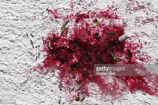 bottle of red wine smashed on a wall - wine stain stockfoto's en -beelden