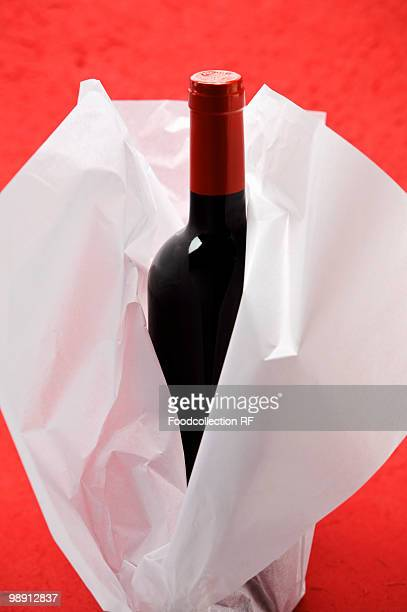 Bottle of red wine wrapped in tissue paper, close-up